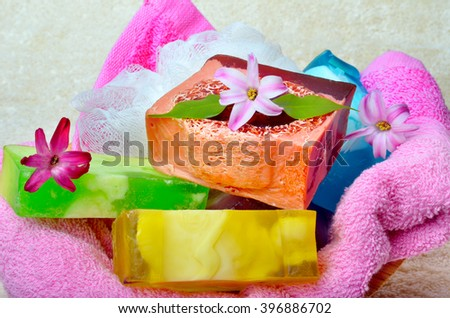 Handmade soap with flowers on a background colored towels. - stock photo