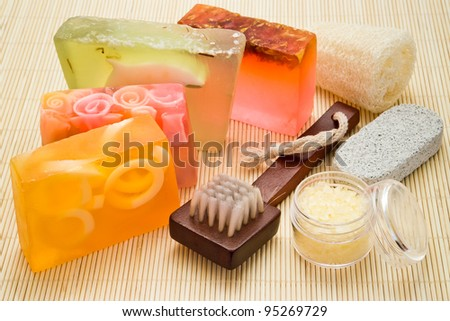 handmade soaps with brush loofah and sea-salt on bamboo board