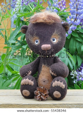 Handmade, the sewed toy: teddy-bear Mocca on a little board among flowers lupine and buttercups