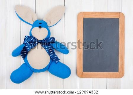 Handmade toy bunny, blackboard on wooden background - stock photo