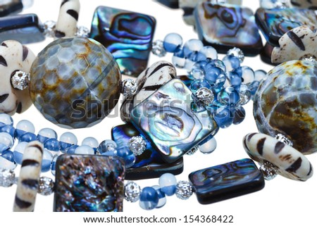 handmade women blue necklace from glass, carved bone and nacre close up - stock photo