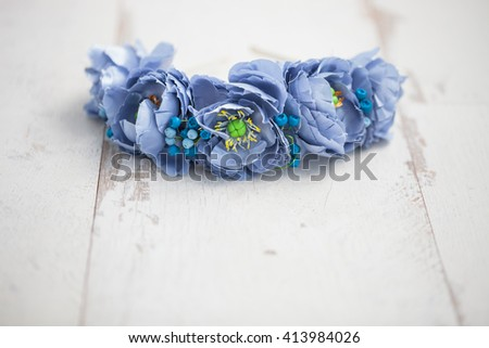 Handmade wraith made of artificial blue flowers lying on the bright white wooden background. Shallow depth of field, macro close up, copy space on the bottom - stock photo