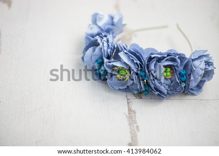 Handmade wraith made of artificial blue flowers lying on the bright white wooden background. Shallow depth of field, macro close up, copy space on the left side - stock photo