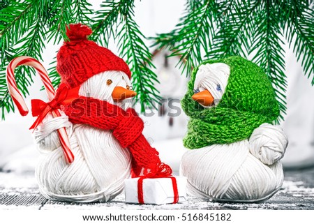 Handmade yarn snowman giving gift box and candy cane to his snow girlfriend under evergreen branches