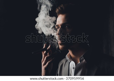 Handome man in suit on the black background smoking a cigar - stock photo