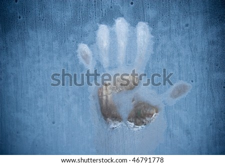 Handprint on a frozen window (symbolizing horror or fear) - stock photo