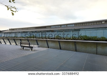 handrail and bench set on pavers with steel grating on public walkway facing building with loading bay across the river - stock photo