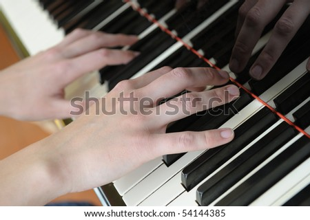 Hands above keys of the piano. A photo close up. - stock photo