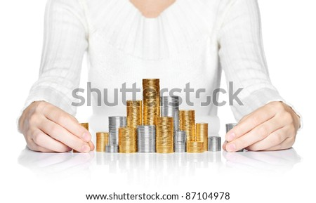 Hands adding a stack of coins to savings - stock photo