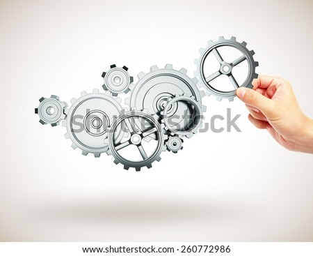 hands adds to gear mechanism on gray background - stock photo