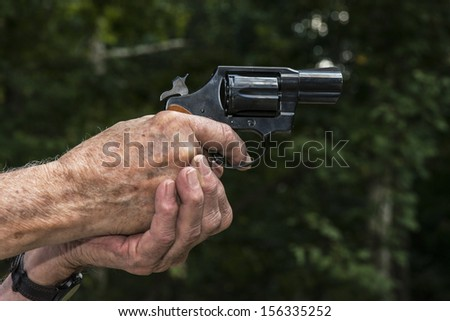 Hands aiming a 38 Detective Special pistol handgun - stock photo