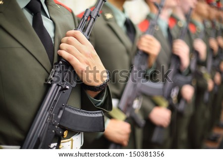 Hands and chests of soldiers in uniforms with machine guns on parade. - stock photo