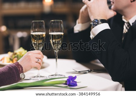 Hands and part of the face of the man and woman sitting in a restaurant by a table and holding glasses with wine. Shelves with wine and candles are on background.