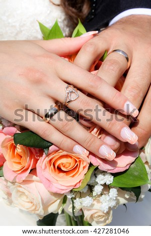 Hands and rings on wedding bouquet. Jewelry concept - hands of couple with ring