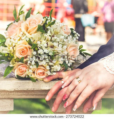 Hands and rings on wedding bouquet. wedding theme background - stock photo