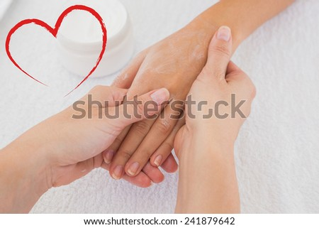 Hands applying cream against heart - stock photo