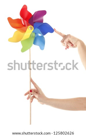 Hands are holding and moving colorful pinwheel toy - stock photo