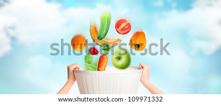 Hands are holding basket against sky background, vegetables, fruits and berries are falling into this basket. Online grocery store concept. Wealth concept. Healthy food concept - stock photo