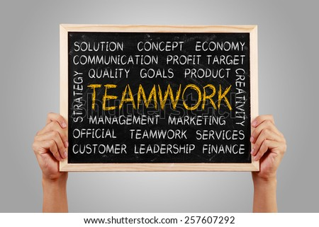 Hands are holding the blackboard of teamwork word cloud with gray background. - stock photo