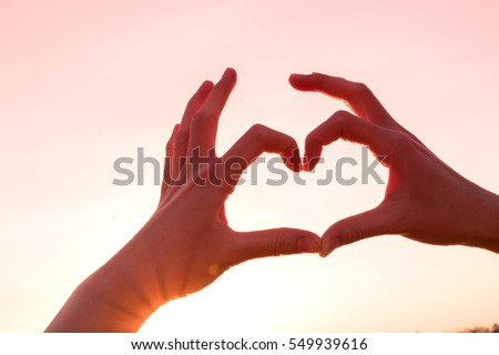 Hands as heart shape with pastel pink romantic background,love concept