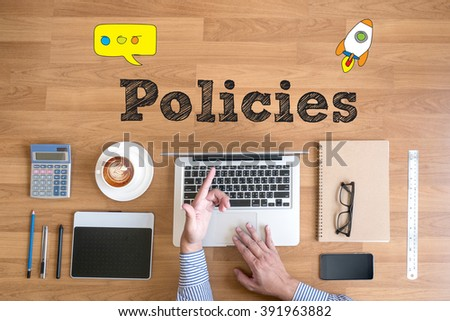 hands at work with financial reports and a laptop with other objects around, coffee,  top view,Policies Concept - stock photo