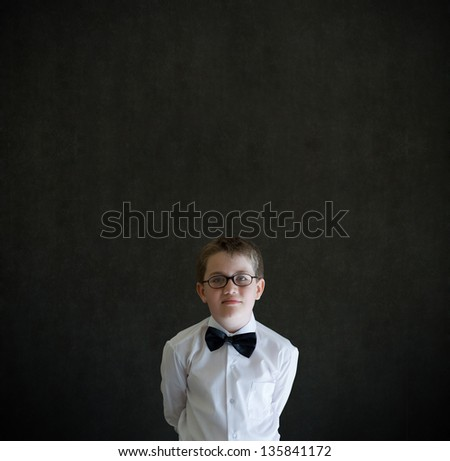 Hands behind back boy dressed up as business man, teacher or student on blackboard background - stock photo