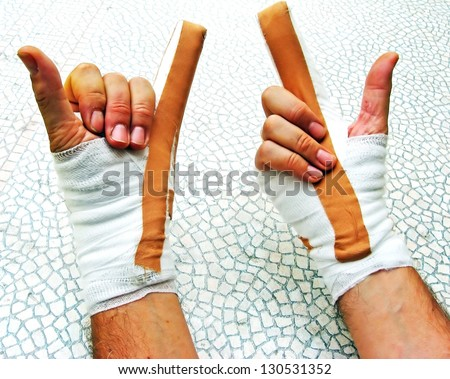hands breaking of bones wrapped in bandages and plasters - stock photo
