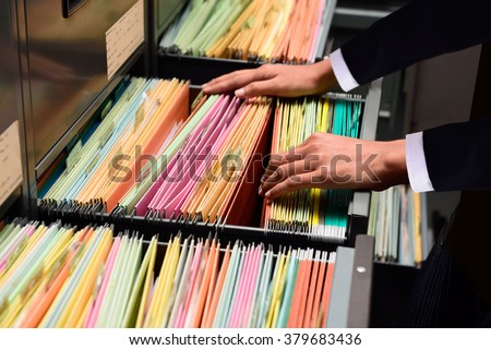 Hands Businessman searching through file folders with personal finance documents
