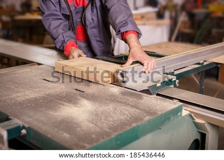 Hands carpenter working on the circular saw - stock photo