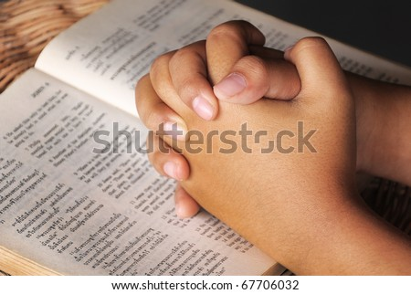 Hands clasped in prayer on Holy Bible - stock photo