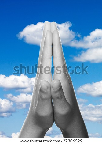 Hands clasped in religious prayer against sky background - stock photo