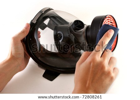 Hands cleaning a black gas mask with a piece of blue cloth - stock photo