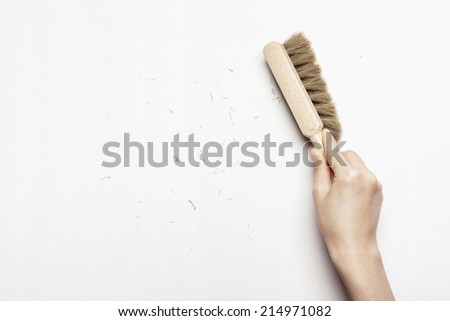 hands cleaning the desk with brush isolated white. - stock photo