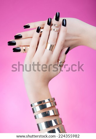 Hands close up of young woman with black manicure wearing gold bracelet and knuckle rings - stock photo