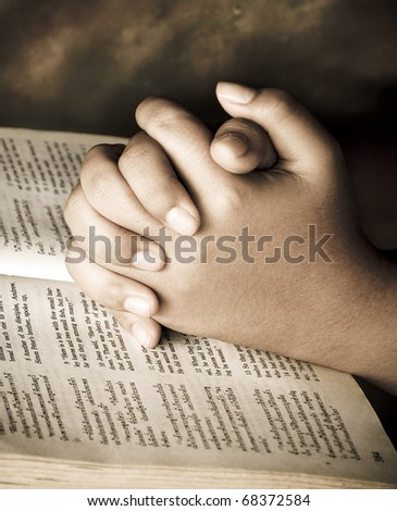 Hands closed in prayer on an open bible - stock photo