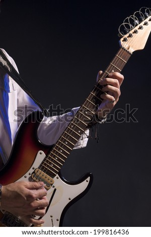 Hands Closeup of Male Guitarist Isolated Over Black Background. Vertical Image