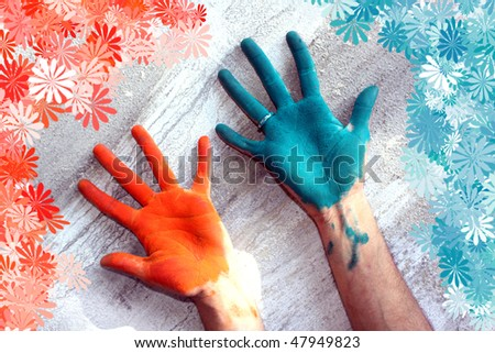 Hands colored with Holi festival colors, with a floral pattern around. - stock photo