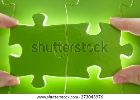 Hands completing puzzle Jigsaw and puzzles concepts - stock photo