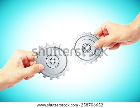 hands connecting  gears on blue background - stock photo