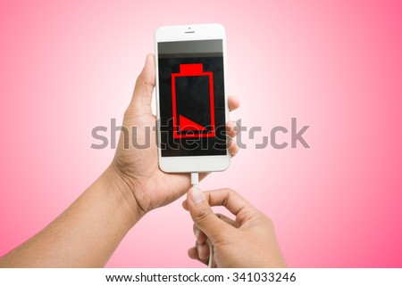 Hands connecting smartphone with low battery to a charger - stock photo