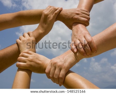 Hands connecting to a chain with blue sky - stock photo