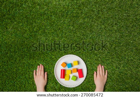 Hands constructing from color wooden blocks over green grass background