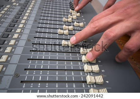 hands controlling professional studio mixing console closeup shot - stock photo