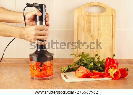 Hands cooks chopped red pepper in a blender - stock photo