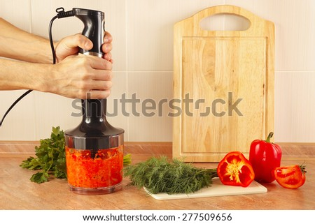 Hands cooks mixed red pepper and tomato in a blender - stock photo