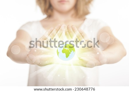 Hands creating a form with shining globe in the center