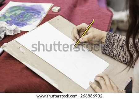Hands drawing with pencil, detail of a street artist in the street - stock photo