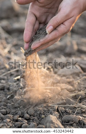 Hands dropping soil and creating dust