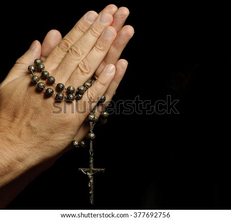 Hands engaged in prayer holding rosary with copy space