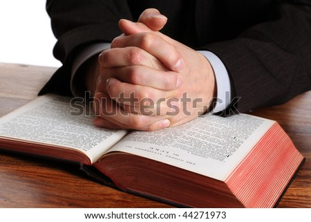 Hands folded in prayer on an open bible - stock photo